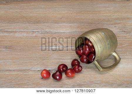 Sweet cherry in the vintage mug lying on a wooden table. Ripe sweet cherries in the old metal mug.