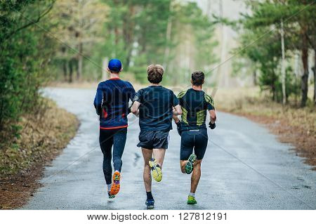 runners three men running down road in woods. feet in a spray of dirt