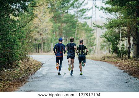 General plan runners three men running down road in Park. feet in a spray of dirt