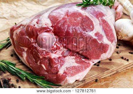 Raw lamb leg on crumpled paper background with herbs.