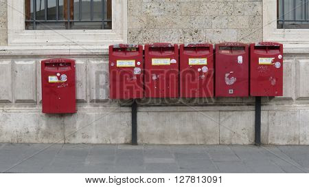 SIENA ITALY - CIRCA APRIL 2016: row of old red letter box mailboxes for sending mail