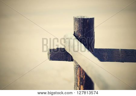 fragment of an old column and poles from a wooden fence for the ranch closeup on an indistinct background in retro style