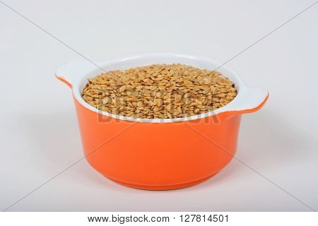 Raw golden linseeds in an orange ramekin dish.