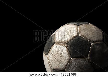Detail of a old black and white soccer ball on a black background with dark shadows
