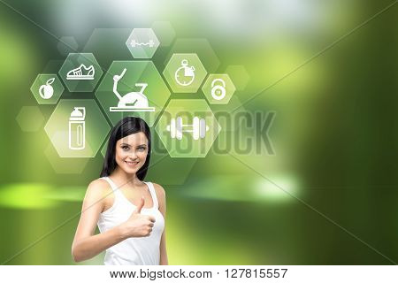 Pretty Caucasian female showing thumbs up and icons with sporting goods on green background