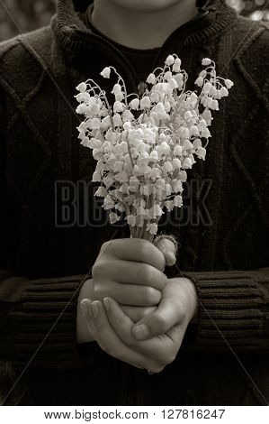 village boy in knit sweater with a bouquet of lilies of the valley white flowers in her hands. selective focus. black and white photo