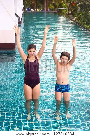 pretty swimmer teenager girl and preteen boy jump exercise in swimming pool water
