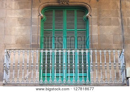 Arched window with closed shutters and balcony