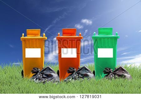 recycle bins and bag garbage on green grass background ecology concept