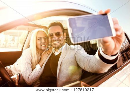 Cropped shot of an affectionate young couple taking a selfie.A young woman and a young man are laughing in the car enjoying in the road trip.
