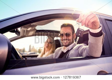 Man and woman bying a car.Men sitting in a car and showing car key. Focus on key.