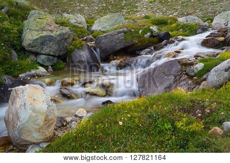Flowing transparent waters among colorful rocks and high altitude flora. Little stream in idyllic uncontaminated environment on the Italian French Alps. Long exposure blurred flowing effect on water.