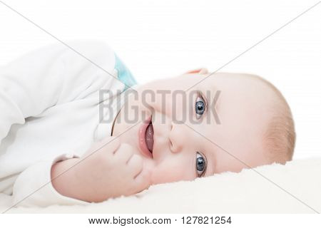 Baby boy lying on a blanketwhite background.He is looking at camera.
