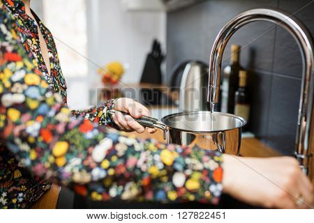 Pouring Water To The Saucepan