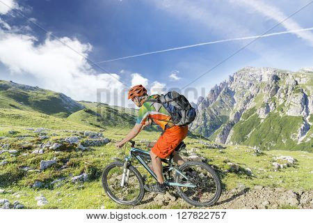 Mountain bike rider with rucksack rides a rocky single trail in the mountains