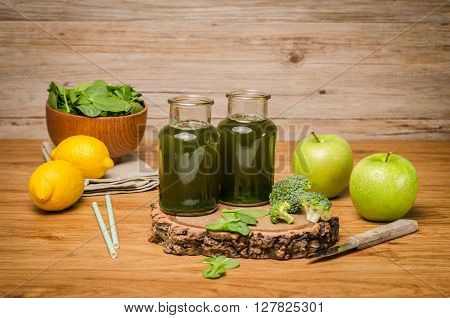 Green fresh leafy greens smoothie in glass jar spinach leaves apple broccoli and lemon. Refreshing healthy drink on wooden table background