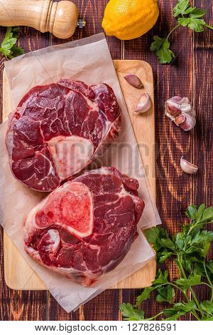 Raw fresh beef meat cross cut for ossobuco on cutting board with ingredients for making gremolata top view.