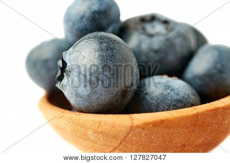 Wooden spoon filled of Ripe bilberry or blueberry over isolated white background