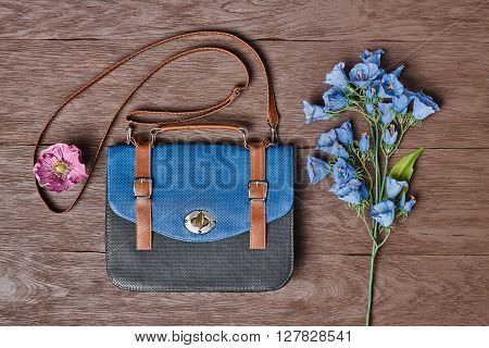 Overhead outfit Fashion ladies accessories. Glamor creative hipster look, pastel colors. Stylish handbag, bouquet of blue flowers. Unusual modern summer essentials.Top view on wood, vintage