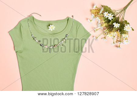 Overhead outfit Fashion Ladies, accessories. Glamor creative  T-shirt, flowers, necklace, bouquet of camomile. Unusual modern elegant essentials.Top view, pink background