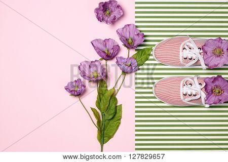 Overhead outfit Fashion girl clothes set, accessories. Creative hipster look. Stylish gumshoes and purple flowers. Unusual modern summer essentials. Top view, pink greeen background, copy space