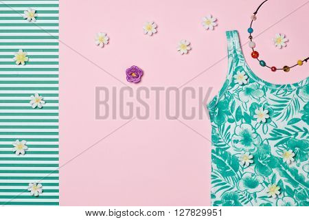 Overhead outfit Fashion woman clothes set, accessories. Glamor creative hipster look, pastel colors. Stylish necklace, flowers. Unusual modern summer essentials. Top view, pink green background