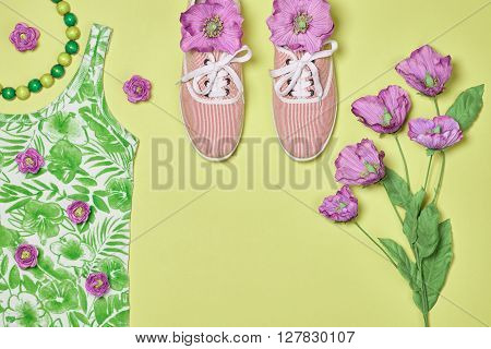 Overhead outfit Fashion ladies clothes set, accessories.Glamor creative hipster look, pastel colors. Stylish gumshoes, necklace, flowers. Unusual modern summer essentials.Top view, green background