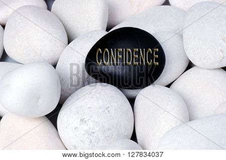 Confidence Concept text on stones stand out of crowd concept.