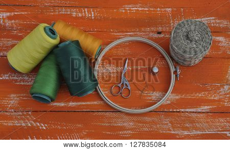 threads in the coil and crafts items on the old wooden table orange
