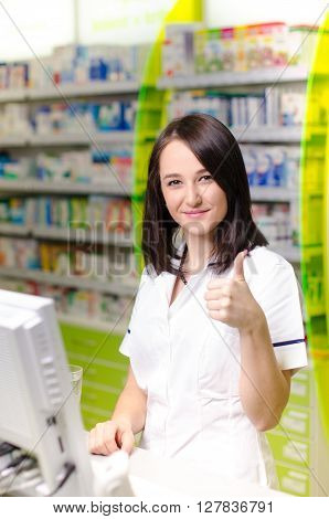 Pharmacist chemist woman stand behind a computer. Pharmacy drugstore is background. Pretty, young woman. Pharmaceutical. Show a gesture