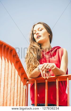 Young long haired girl leaning against railing on the urban bridge. Lifestyle funky in summer. Trendy sport teen.