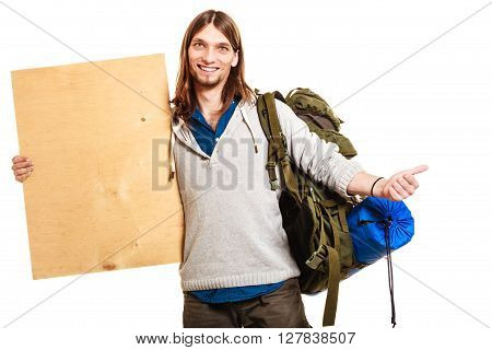 Man tourist backpacker holding blank wood plank copy space. Young guy hitchhiking with thumb up gesture. Male hiker backpacking. Summer vacation travel.