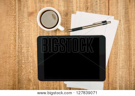 Black pad screen on wooden table with coffee paper sheets and pen. Topview Mock up