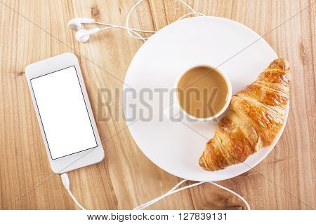 Wooden desktop with blank white smartphone coffee and croissant. Topview Mock up