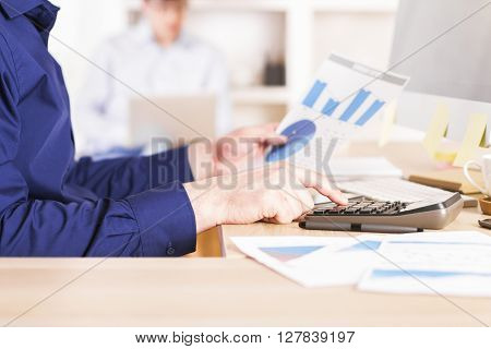 Sideview of businessman using calculator on business diagrams