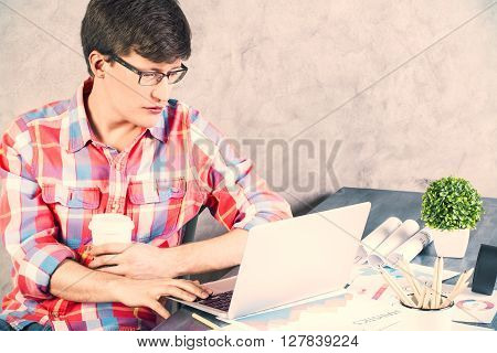 Sideview of caucasian male with coffee in hand using laptop on office desk with items. Concrete wall background