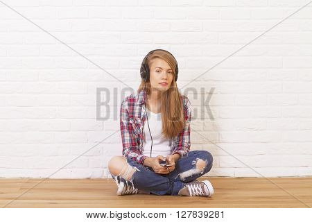 Pretty Caucasian girl sitting on wooden floor in studio and listening to music. White brick wall background