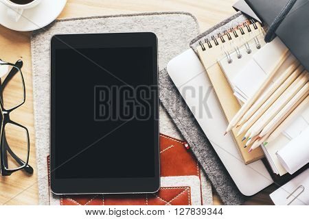 Topview of table with blank tablet on case and office tools. Mock up