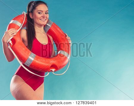 Happy lifeguard with ring buoy lifebuoy. Woman girl supervising swimming pool water on blue.