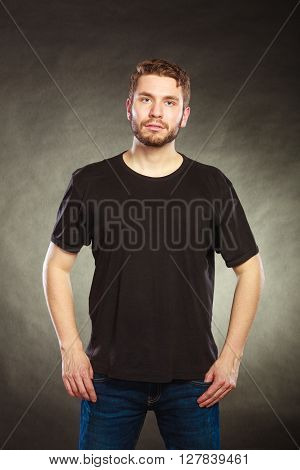 Portrait of handsome fashionable man in black blank shirt with empty copy space. Young guy in studio on black. Casual fashion advertisement.