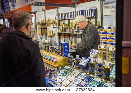 STRASBOURG FRANCE - APR 24 2016: Man buying traditional French fish preserves at the traditional french covered market