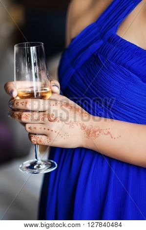 Wineglass in woman hands with mehendi and blue dress