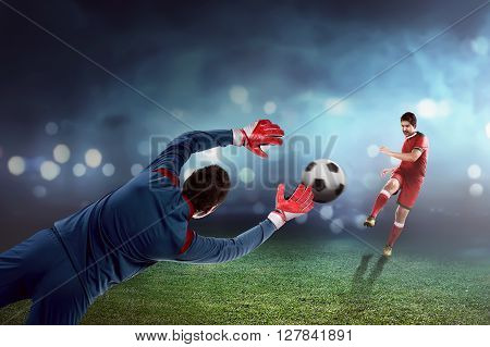 Football player kick ball and goalkeeper try to catch