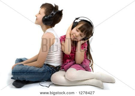 Brother And Sister Listening To Headphones