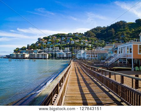 A boardwalk leading to seaside town. Beachfront houses along the way.