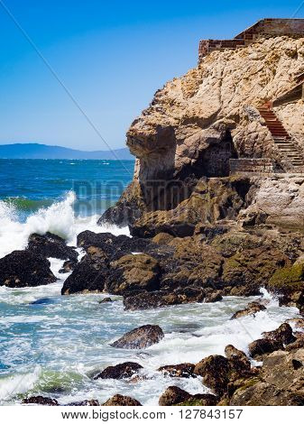 A scene with ocean waves crashing against rock cliffs in the ocean. Mountains and clear blue sky in the distance.