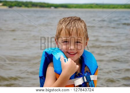 Adorable boy in a life vest smiling at the lake.