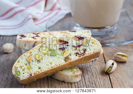 Biscotti with cranberry and pistachio with cup of coffee latte closeup
