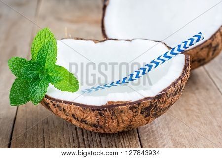 Natural organic coconut water in cracked coconut on wooden table
