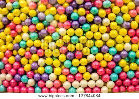 Multi-colored candy drops in a bulk food bin